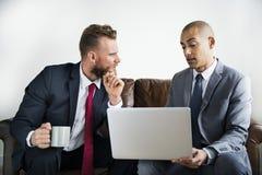 两个不同的商人坐长沙发 免版税库存图片