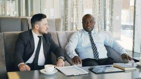 两个不同种族的商人谈论起始的想法在玻璃状咖啡馆在午餐时间 咖啡杯,财政图表和 影视素材