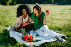 两个不同种族的美丽的微笑的女朋友是聊天和浏览通过手机,当吃时 免版税库存照片
