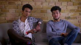 两个与是的兴奋一起的年轻男性朋友看着电视特写镜头射击在长沙发的放松的开会户内 影视素材