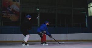 两个专业曲棍球运动员去到战斗的旅大市为顽童 力量招待会 股票视频