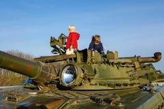 两个严肃的男孩攀登了一辆军事坦克的装甲 免版税库存照片