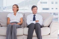 两个乏味商人坐长沙发 免版税库存照片