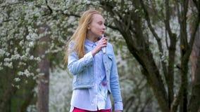 两个乐趣孩子女孩获得弹有长的金发的乐趣蓝色吉他摇她的在公园的头 春天心情微笑laug 股票录像
