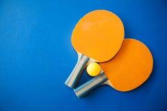 两个乒乓球或乒乓球球拍和球在一张蓝色桌上 库存照片
