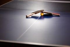 两个乒乓球或乒乓球球拍和球在一张蓝色桌w上 库存照片