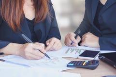 两个亚洲人谈话和在办公室的女商人包括财政图表,计算器 图库摄影