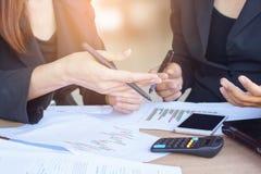 两个亚洲人谈话和在办公室的女商人包括财政图表,计算器 免版税库存照片