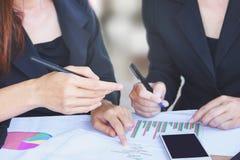 两个亚洲人谈话和在办公室的女商人包括财政图表,计算器 免版税库存图片