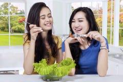 两个亚裔女孩吃新鲜的沙拉 库存照片