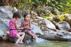 两个亚裔小孩女孩坐岩石和戏剧浇灌 库存图片