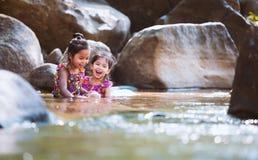 两个亚裔小孩女孩坐岩石和戏剧浇灌 库存照片