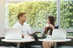 两个亚裔工友一起使用膝上型计算机和智能手机工作havi 免版税图库摄影
