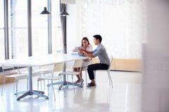 两个人与数字式片剂一起使用在空的会议室 库存图片