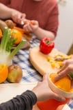 两个人与新鲜的水果和蔬菜一起烹调 库存图片