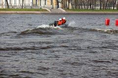 两个人乘坐有马达的一条可膨胀的小船 儿童` s wate 库存图片
