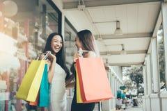 两个人亚裔妇女滑稽和愉快关于购物在出口 库存图片