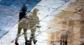 两个人和一条狗的模糊的反射阴影在湿路面 免版税库存照片