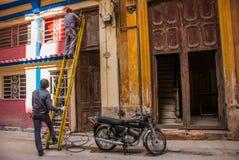 两个人和修理在家架线的梯子,摩托车在街道上停放 哈瓦那 古巴 库存照片