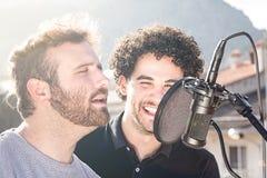 两个人唱歌 唱歌在街道和一个与蓬松卷发头发 库存图片