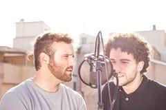 两个人唱歌 唱歌在街道和一个与蓬松卷发头发 免版税库存照片