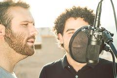 两个人唱歌 唱歌在街道和一个与蓬松卷发头发 图库摄影