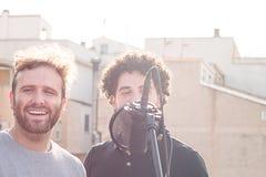 两个人唱歌 唱歌在街道和一个与蓬松卷发头发 免版税库存图片