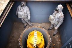 两个人在化工保护衣服埋葬化学制品穿戴了 免版税库存图片