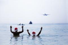两个人在圣诞老人红色帽子在早晨招呼致敬飞机 库存图片
