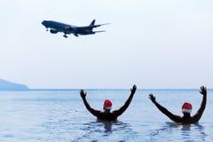 两个人在圣诞老人红色帽子在早晨招呼致敬飞机 图库摄影