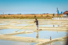两个人在盐沼收获盐用传统方式 免版税库存照片