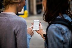 两个人在看他们的电话和等待Ly的纽约 免版税库存图片