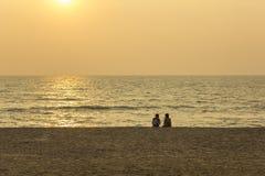 两个人坐一个空的沙滩以海洋和晚上为背景 免版税库存照片