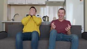 两个人坐长沙发手表在电视和支持不同的队的一足球赛 股票视频