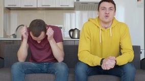 两个人坐长沙发手表在电视的一足球赛和享受他们喜爱的队胜利  股票录像
