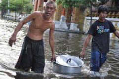 两个人带来难民的免费食物曼谷,泰国一条被充斥的街道的, 2011年10月31日 免版税库存照片