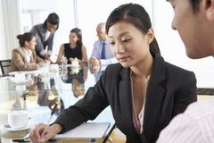 两个人开会议在玻璃表附近在有同事的会议室在背景 免版税图库摄影