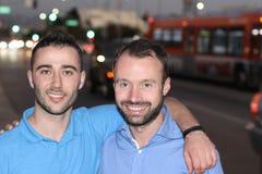 两个人微笑的走城市街道在晚上 库存照片