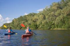 两个人旅行划皮船的河 免版税库存照片