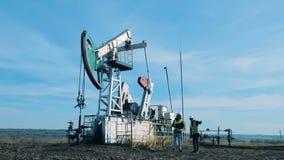 两个人检查一个运作的油塔 矿物燃料,石油工业概念 股票视频