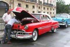 两个人检查一辆红色经典汽车的引擎 免版税库存图片