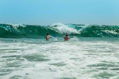 两个人潜水入波浪 库存图片