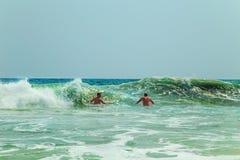 两个人潜水入波浪 免版税库存图片