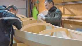 两个人独立地做小船木头 他们自己发明了船的设计他们的旅行的 股票录像