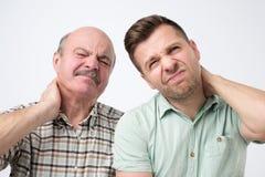两个人生遭受充满脖子痛的ans儿子 免版税库存照片