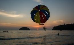 两个人登陆在paraseiling的在日落,极端体育 免版税库存图片