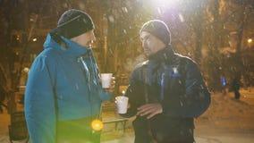 两个人的乐趣交谈在镇中心在冬天用温暖的咖啡在手中 影视素材