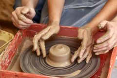 两个人的手创造罐,陶瓷工` s轮子 教的瓦器 免版税库存照片
