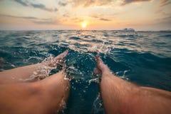 两个人的腿的图象飞溅蓝绿色海水的在日落 免版税库存图片