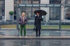 两个人站立在公共汽车站,他们中的一个是哀伤的,别的是ch 免版税库存照片